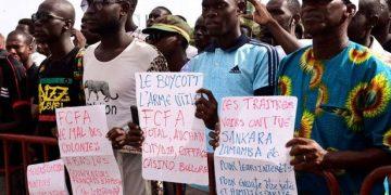 人们在9月16,2017的达喀尔方尖碑广场反对殖民地法郎的反殖民示威期间举着牌子。 与欧元挂钩的非洲金融共同体法郎在该地区的八个西非国家使用,其中六个是法国殖民地。 / AFP PHOTO / SEYLLOU